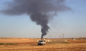 Rebel fighters ride a military vehicle near rising smoke from al-Bab city, northern Aleppo province, Syria