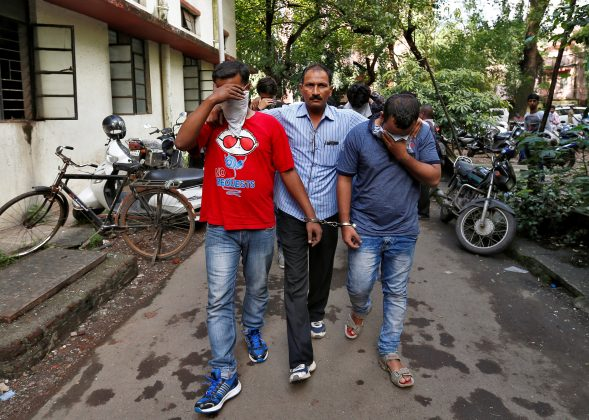 A policeman escorts men who they said were arrested on Wednesday on suspicion of tricking American citizens into sending them money by posing as U.S. tax officials, at a court in Thane, on the outskirts of Mumbai, India