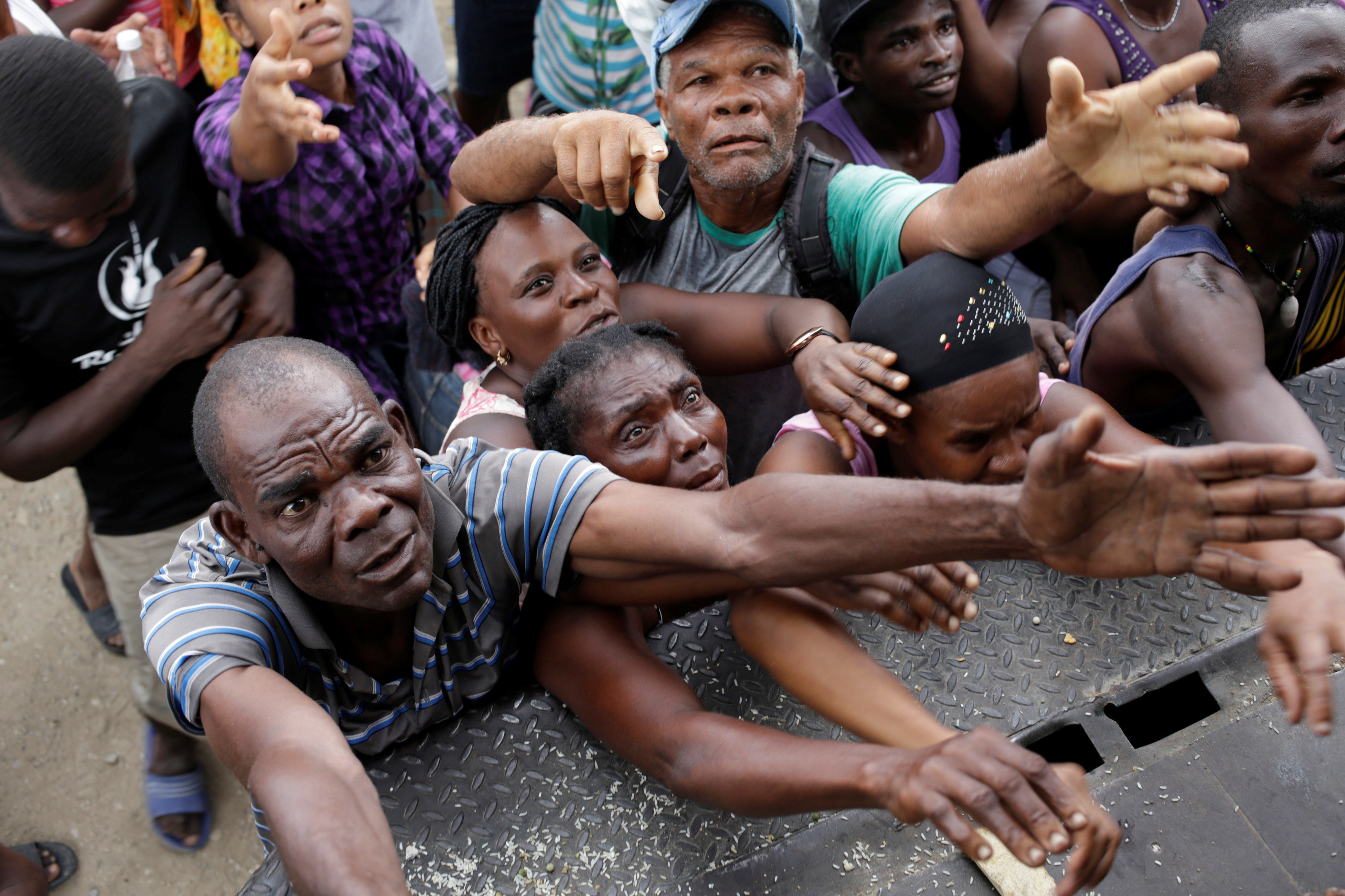 Residents ask for food at the end of a food distribution after Hurricane Matthew in Saint Jean du Sud, Haiti,
