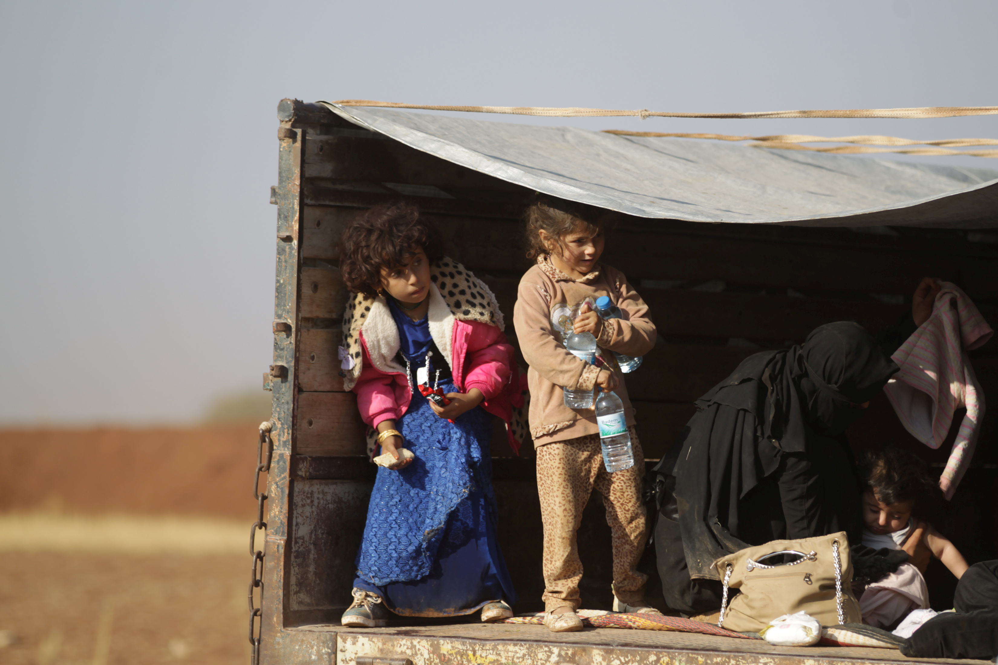 Iraqi refugees that fled violence in Mosul ride a pick-up truck upon arrival in al-Kherbeh village, in Syria's northern Aleppo province.