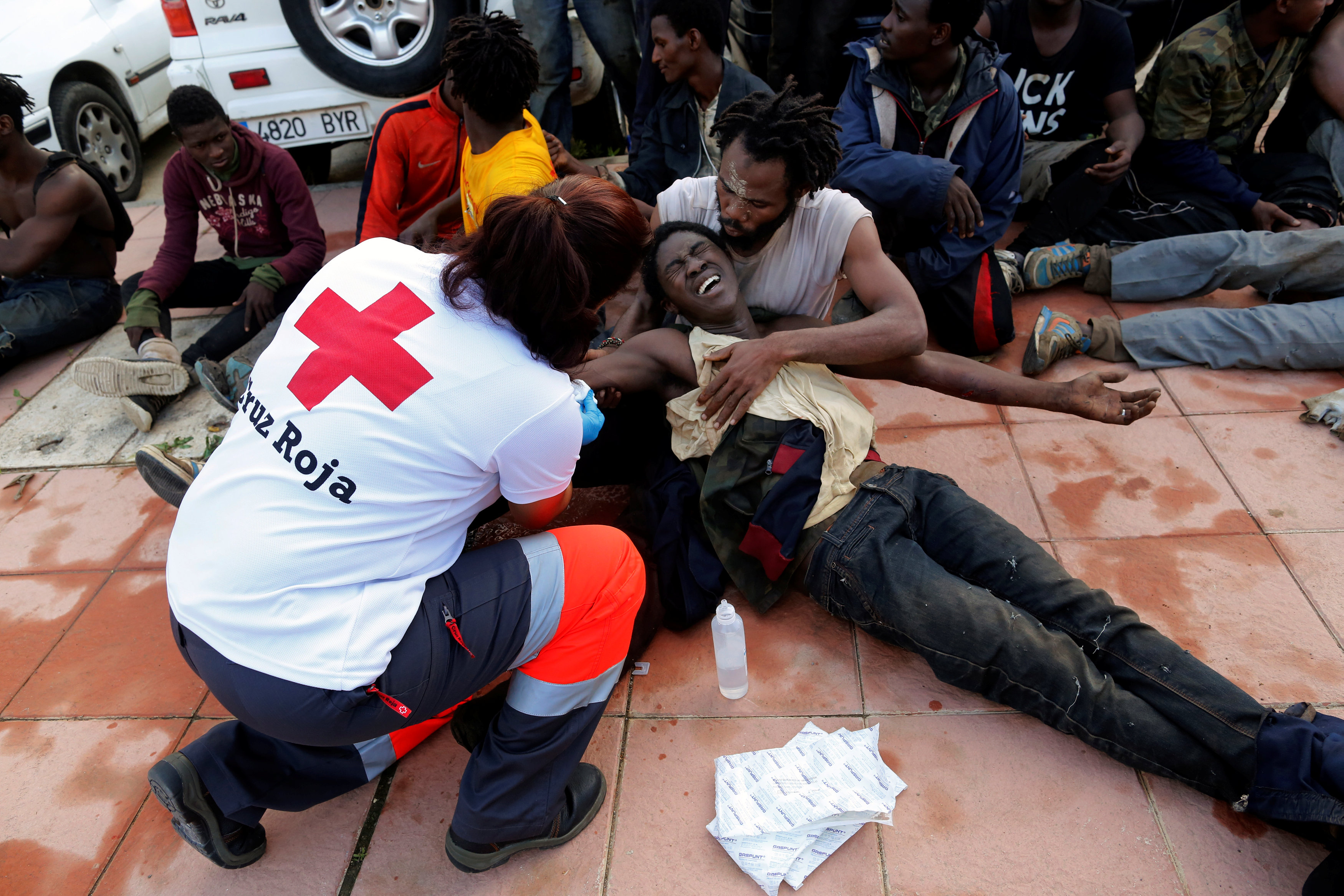 A Spanish Red Cross worker aids African migrants after they crossed a border fence between Morocco and Spain's north African enclave of Ceuta