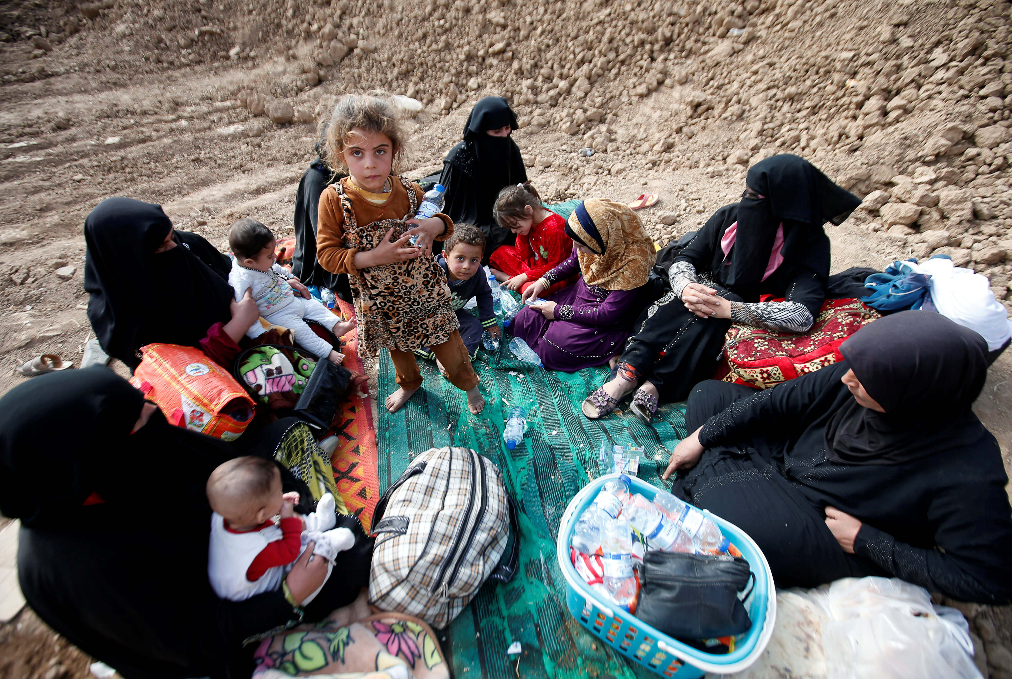 Iraqi women and children sit near the berm after escaping from the Islamic State-controlled village of Abu Jarboa,