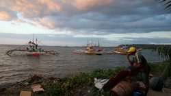 A fisherman look at the fishing boats that just returned from disputed Scarborough Shoal, as they are docked at the coastal village of Cato in Infanta, Pangasinan in the Philippines,