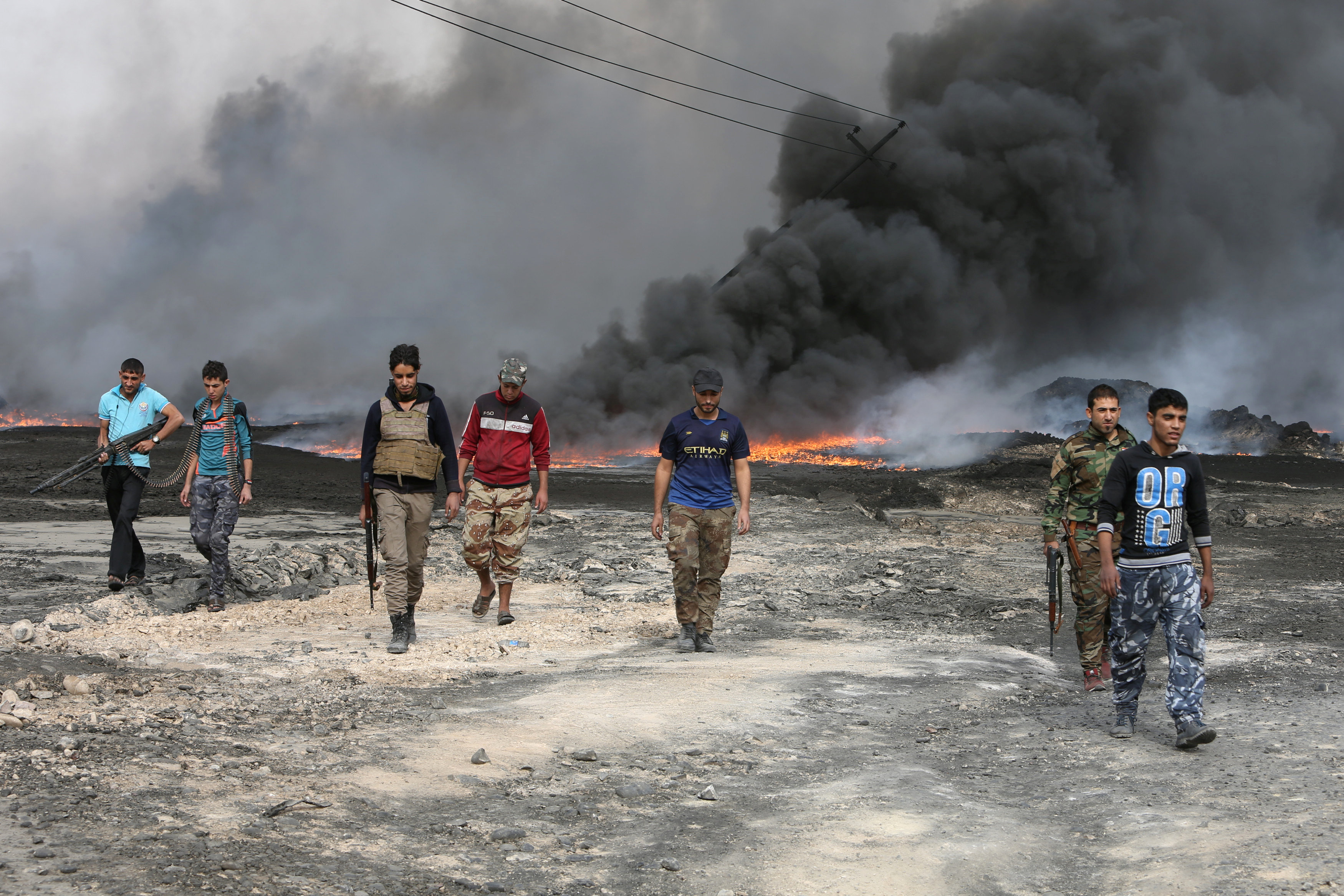 Tribal fighters walk as fire and smoke rises from oil wells, set ablaze by Islamic State militants before IS militants fled the oil-producing region of Qayyara, Iraq,