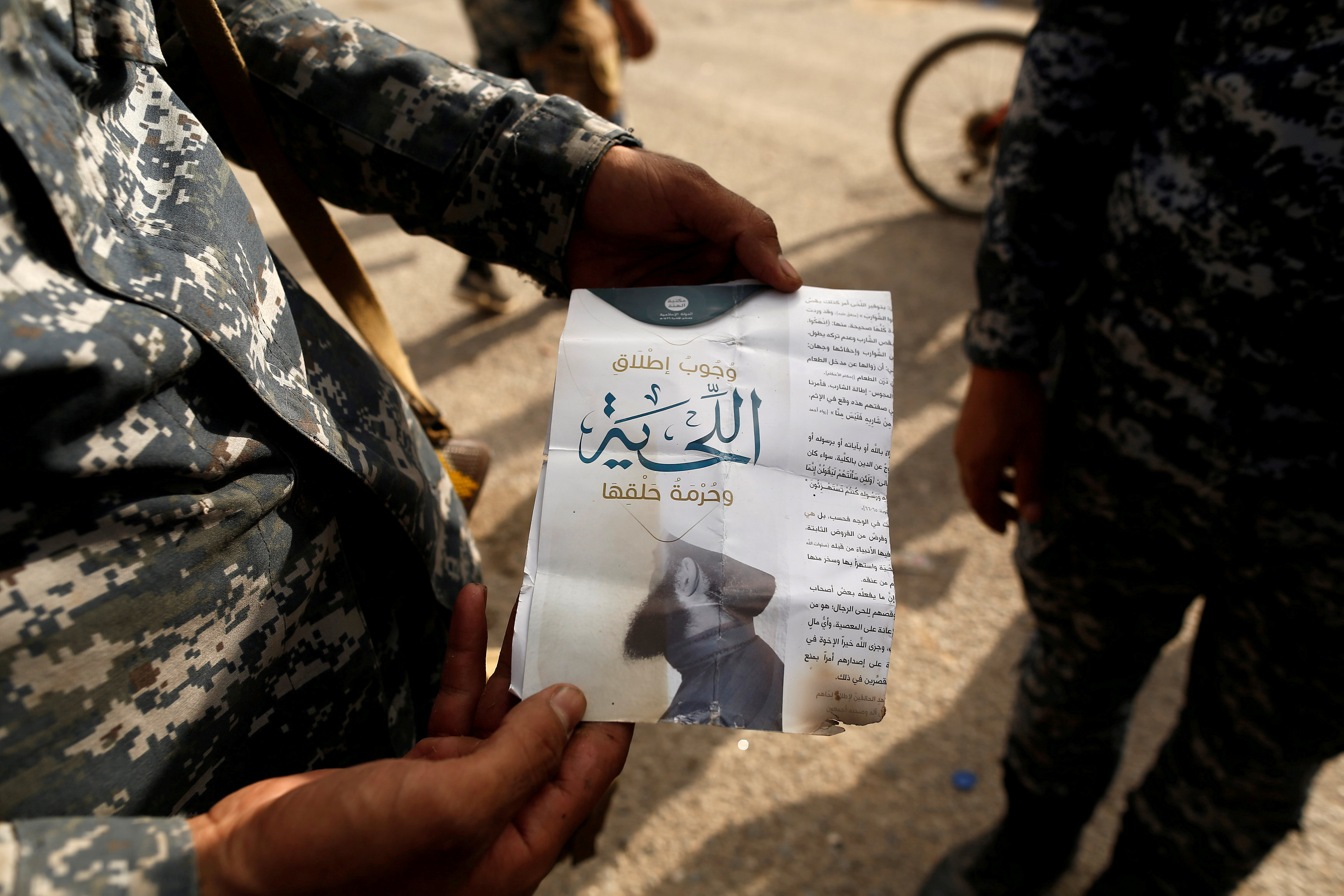 """An Iraqi soldier shows a pamphlet which reads """"Wearing beards is compulsory, shaving is prohibited"""" along a street of the town of al-Shura, which was recaptured from Islamic State (IS) on Saturday, south of Mosul"""