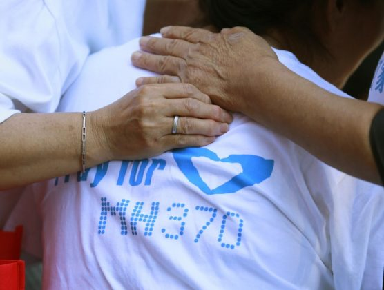 Family members of passengers onboard the missing Malaysia Airlines Flight MH370 comfort a crying woman as they gather to pray at Yonghegong Lama Temple in Beijing September 8, 2014, on the six-month anniversary of the disappearance of the plane.