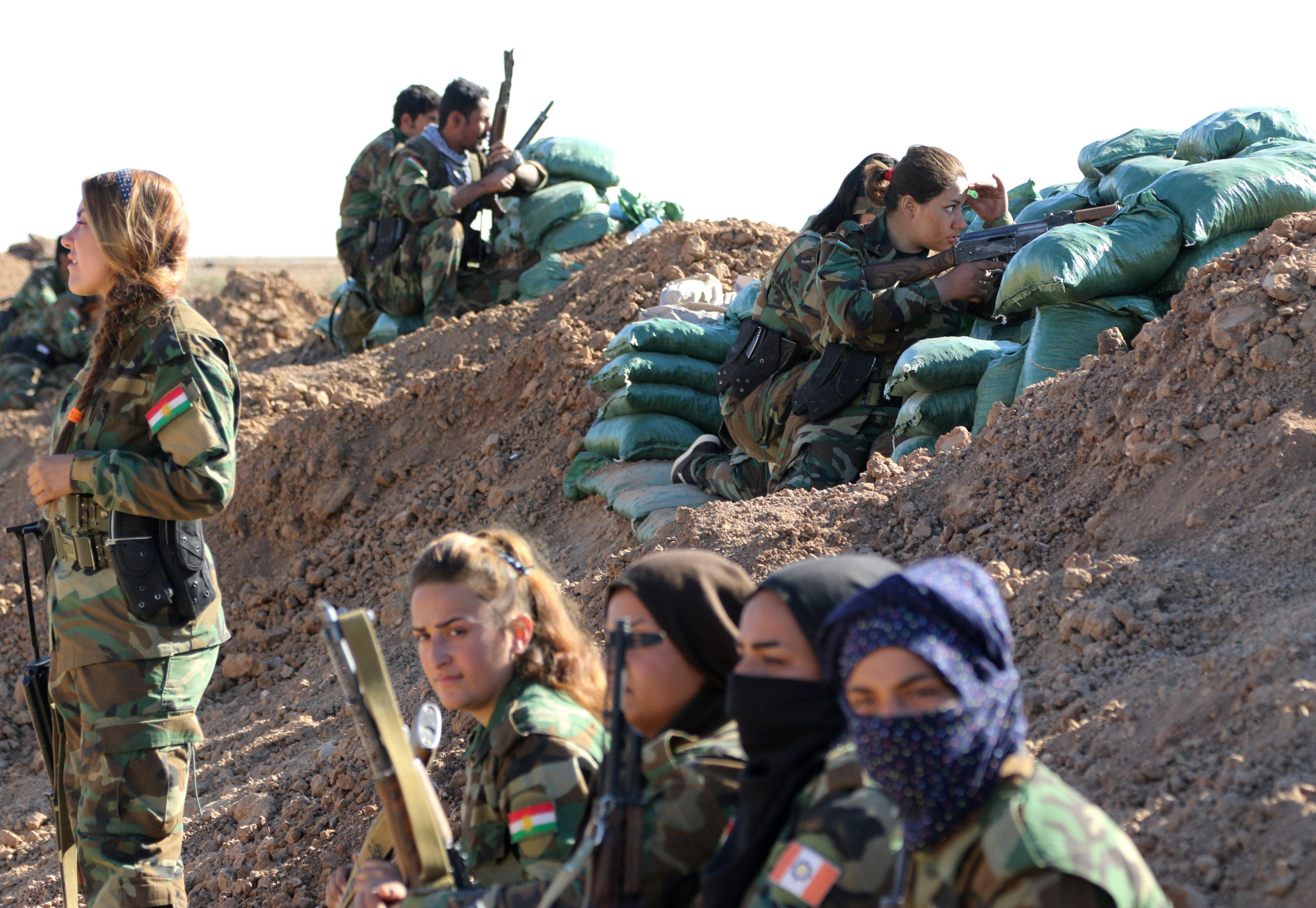 Iranian-Kurdish female fighters sit near a sand berm during a battle with Islamic State militants in Bashiqa, near Mosul, Iraq