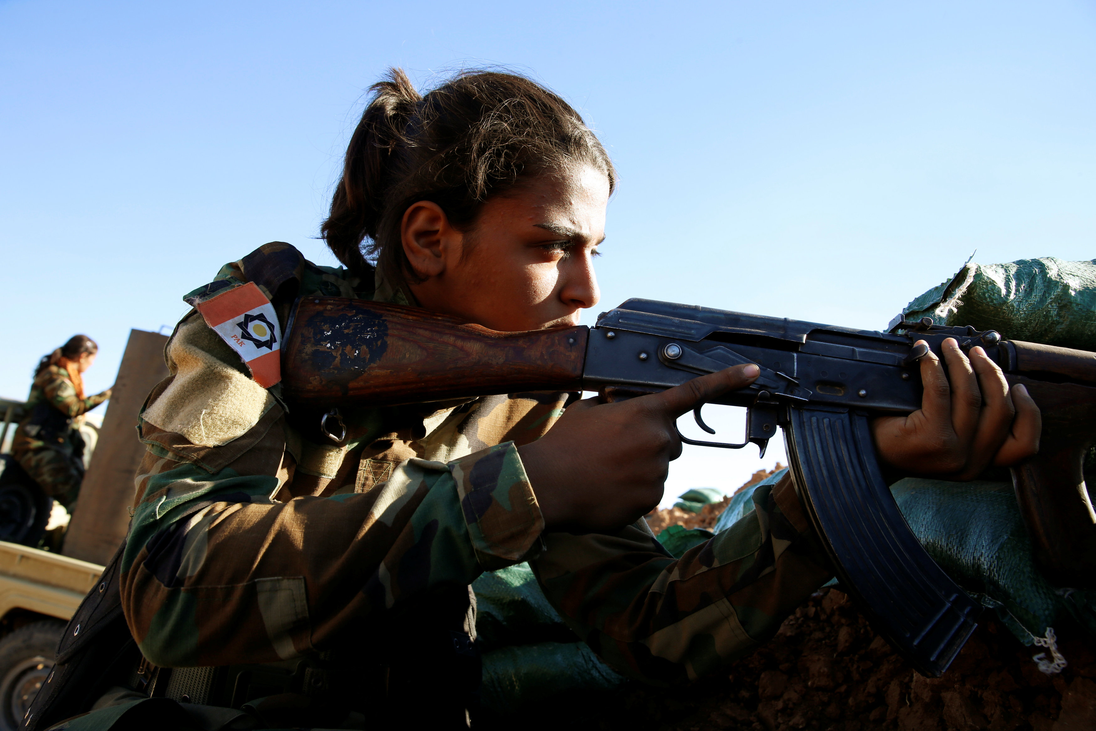 An Iranian-Kurdish female fighter fires her rifle during a fight with Islamic State militants in Bashiqa, near Mosul, Iraq