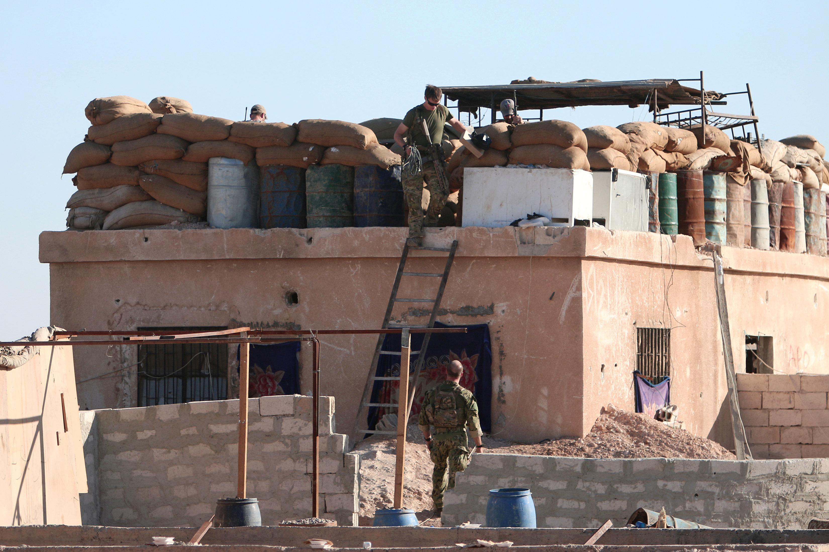 A U.S. fighter walks down a ladder from a barricade, north of Raqqa city, Syria
