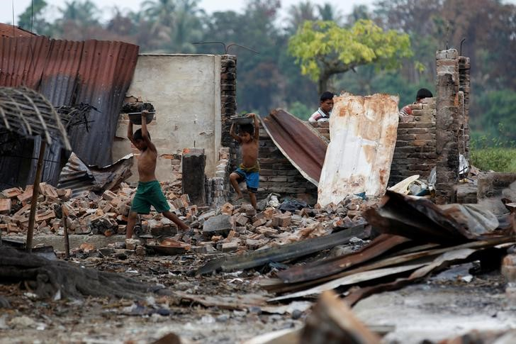 Children recycle goods from the ruins of a market which was set on fire at a Rohingya village outside Maugndaw in Rakhine state, Myanmar,