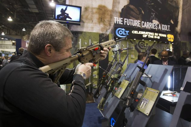 Mark Heitz, of Tactical Firearms in Kingston, New Hampshire, looks over a civilian version of the Colt M4 carbine during the annual SHOT (Shooting, Hunting, Outdoor Trade) Show in Las Vegas