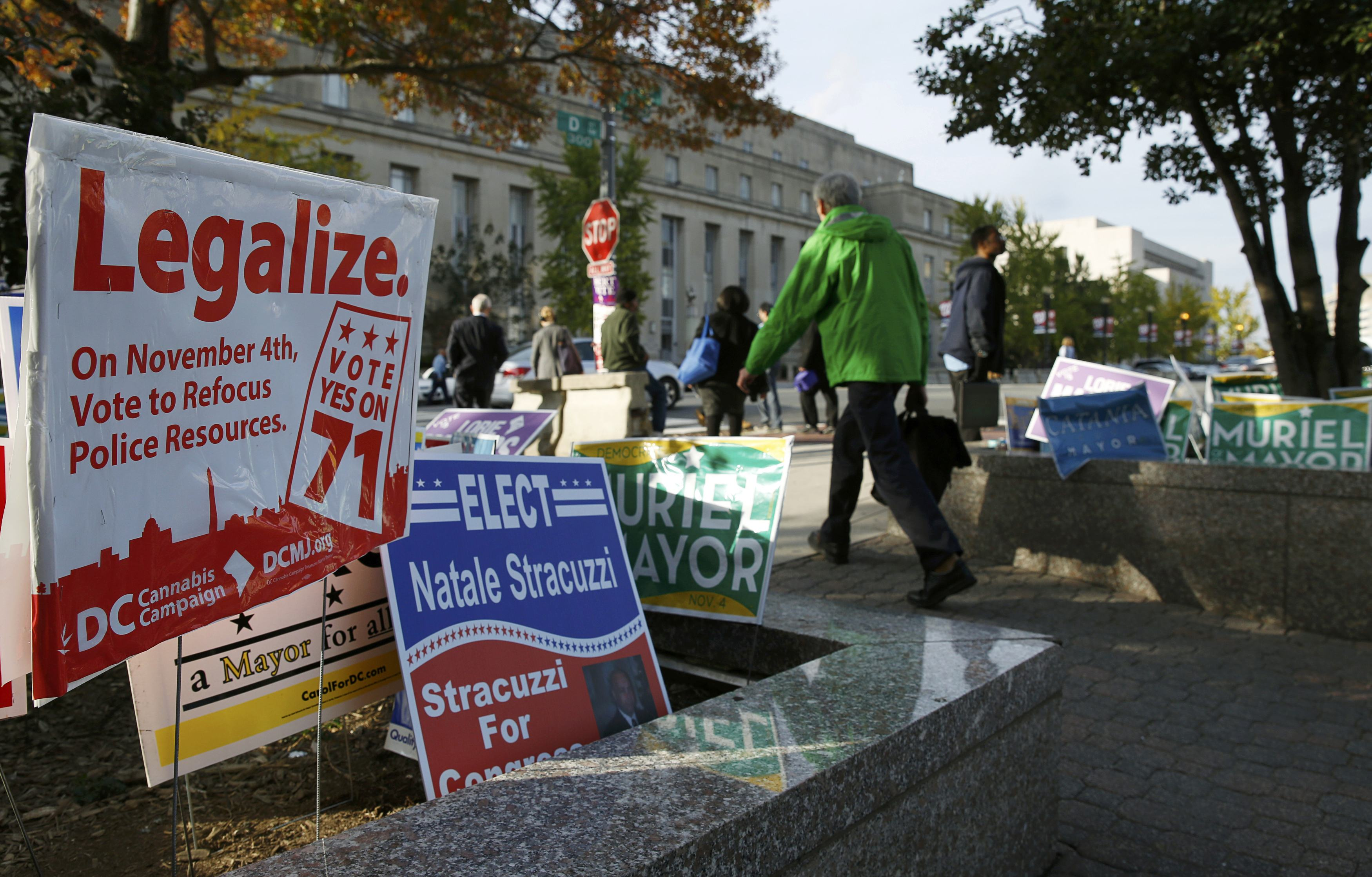 Pedestrians pass by a DC Cannabis Campaign sign in Washington