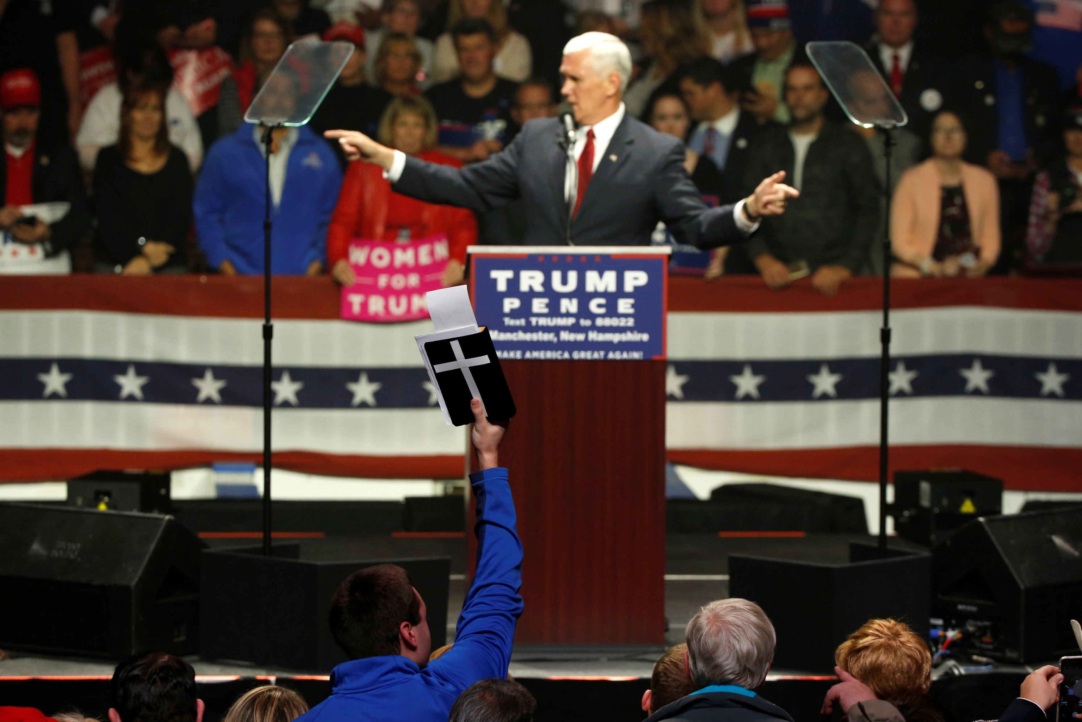 A supporter holds up a Bible as Republican U.S. vice presidential nominee Mike Pence speaks before presidential nominee Donald Trump arrives at an arena in Manchester, New Hampshire, U.