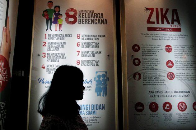 woman near Zika poster