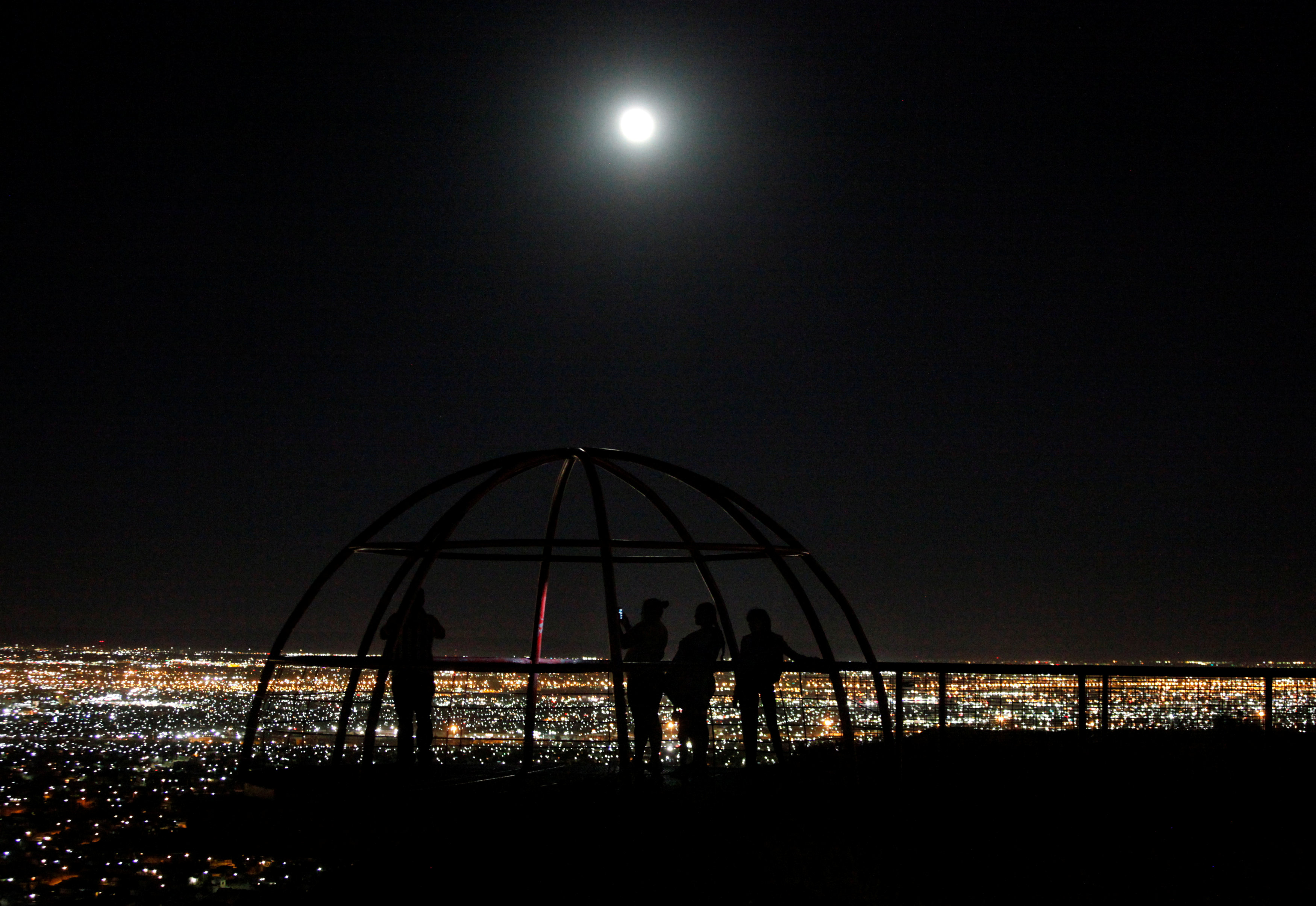 People watch as a supermoon rises over Ciudad Juarez, Mexico, October 16, 2016.