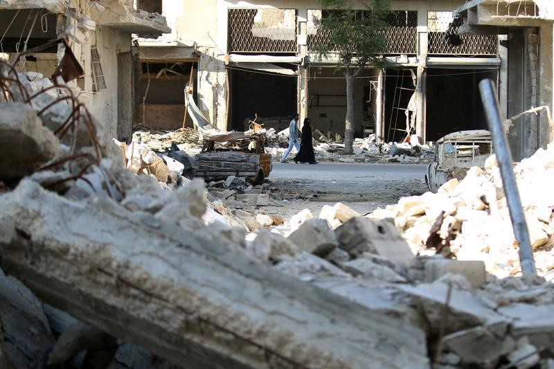 People walk past rubble of damaged buildings in a rebel-held besieged area in Aleppo, Syria