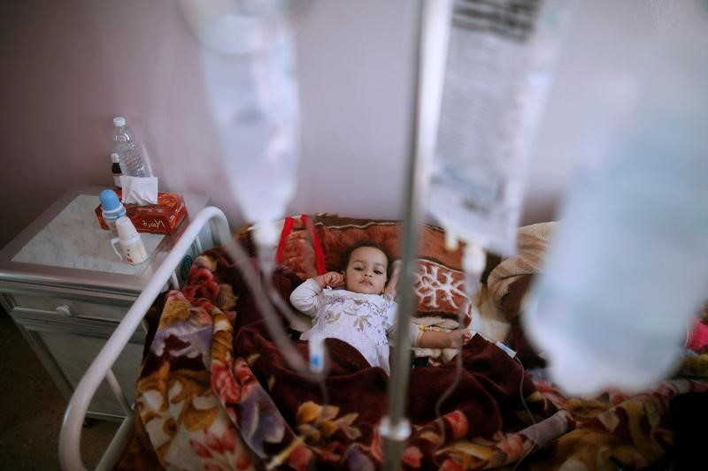 A girl lies on a bed at a cholera treatment center in Sanaa, Yemen,