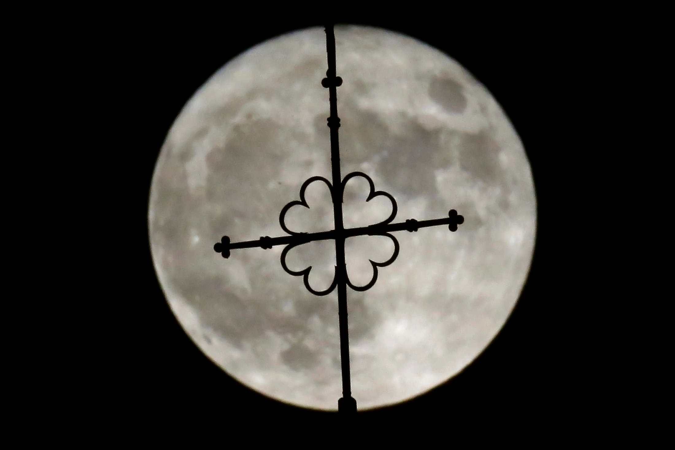 The rising supermoon is seen over the church of Saint-Hilaire in the village of Saint-Fiacre-sur-Maine near Nantes, western France November 14,