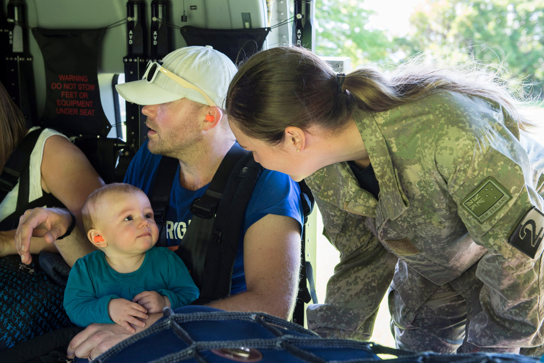 A Royal New Zealand Air Force member (R) helps evacuate a toddler and others aboard an NH90 helicopter from Kaikoura on the South Island of New Zealand