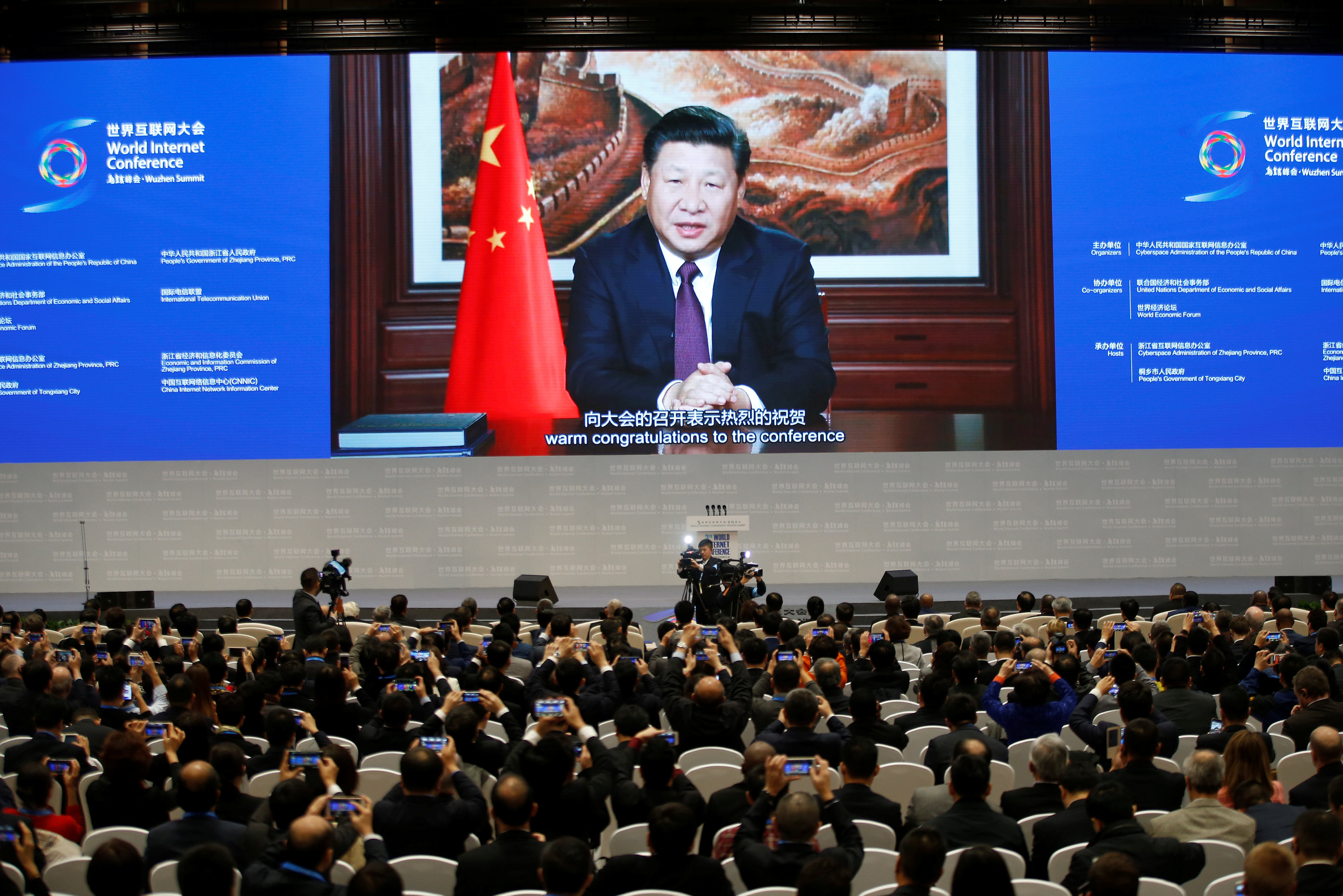 Attendees listen to a speech by China's President Xi Jinping shown on a screen during the opening ceremony of the third annual World Internet Conference in Wuzhen town of Jiaxing, Zhejiang province, China