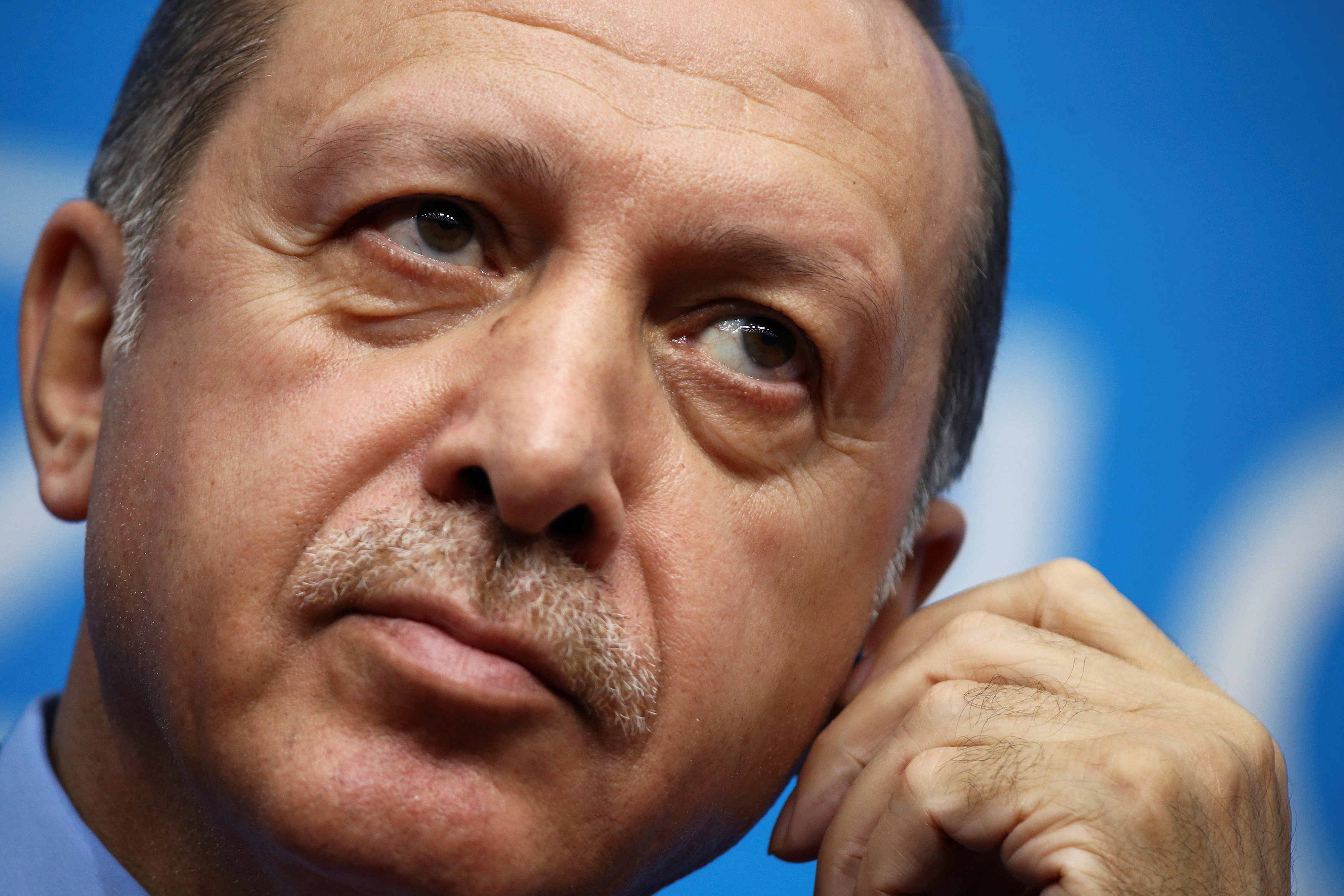 Turkey's President Tayyip Erdogan adjusts earphones during a news conference in Hangzhou, Zhejiang Province, China,