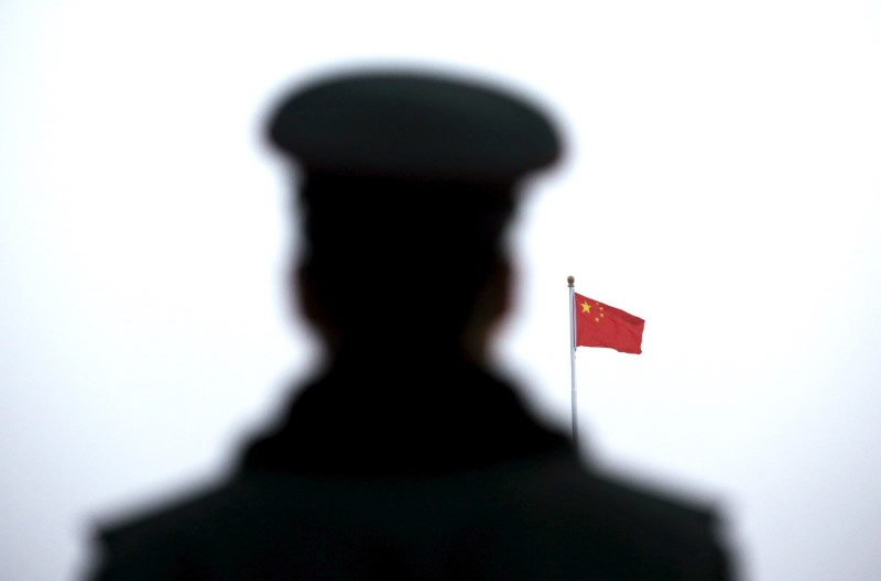 A paramilitary policeman watches a flag-raising ceremony at Tiananmen Square ahead of the opening session of the National People's Congress (NPC) in Beijing, China,