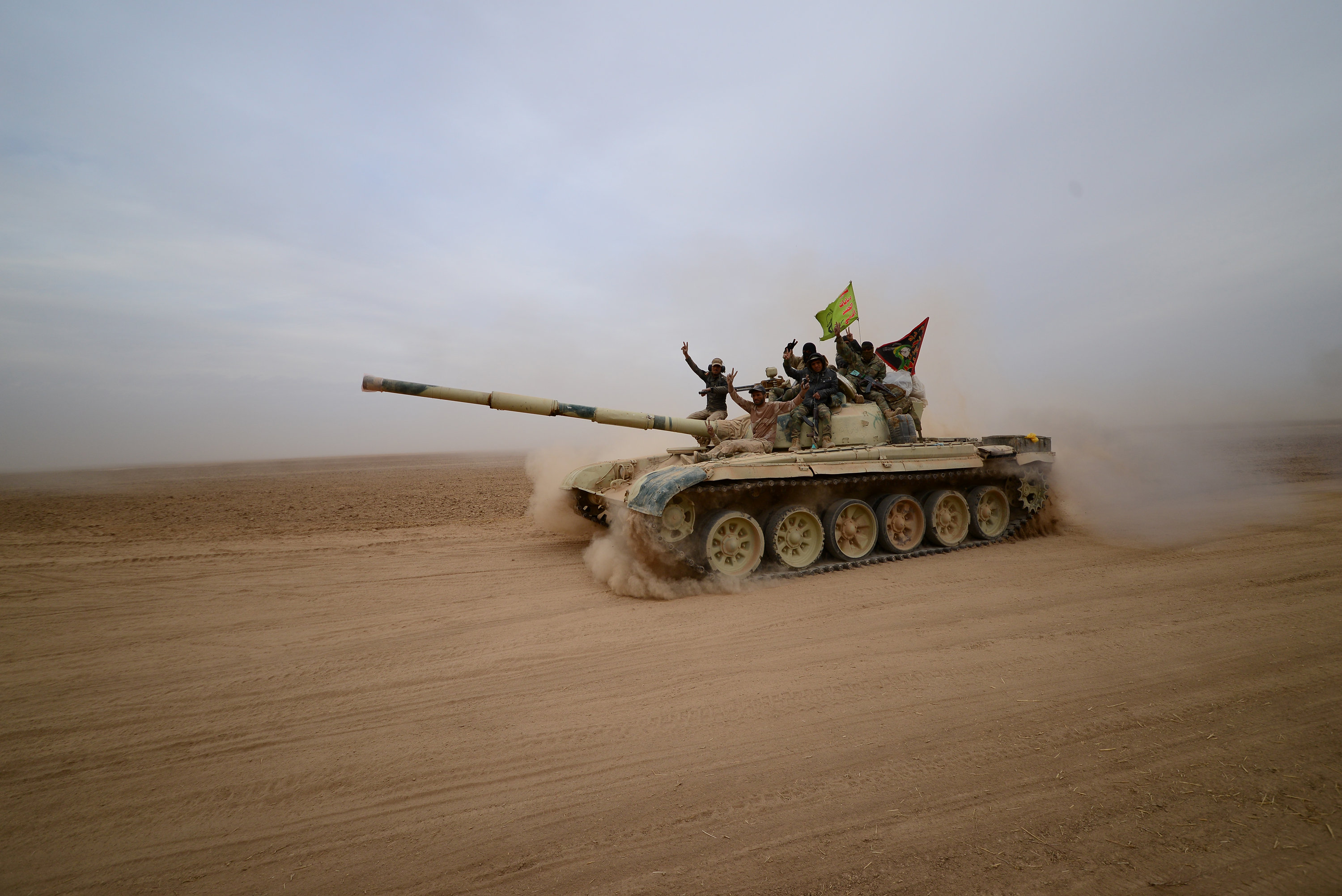 Shi'ite fighters ride on a tank heading toward the airport of Tal Afar during a battle with Islamic State militants in Tal Afar west of Mosul, Iraq
