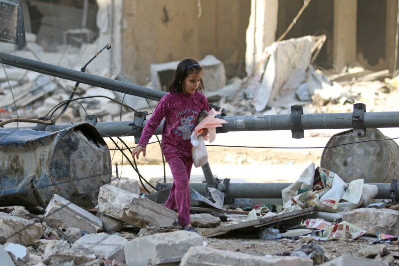 A girl makes her way through the debris of a damaged site that was hit yesterday by airstrikes in the rebel held al-Shaar neighbourhood of Aleppo, Syria