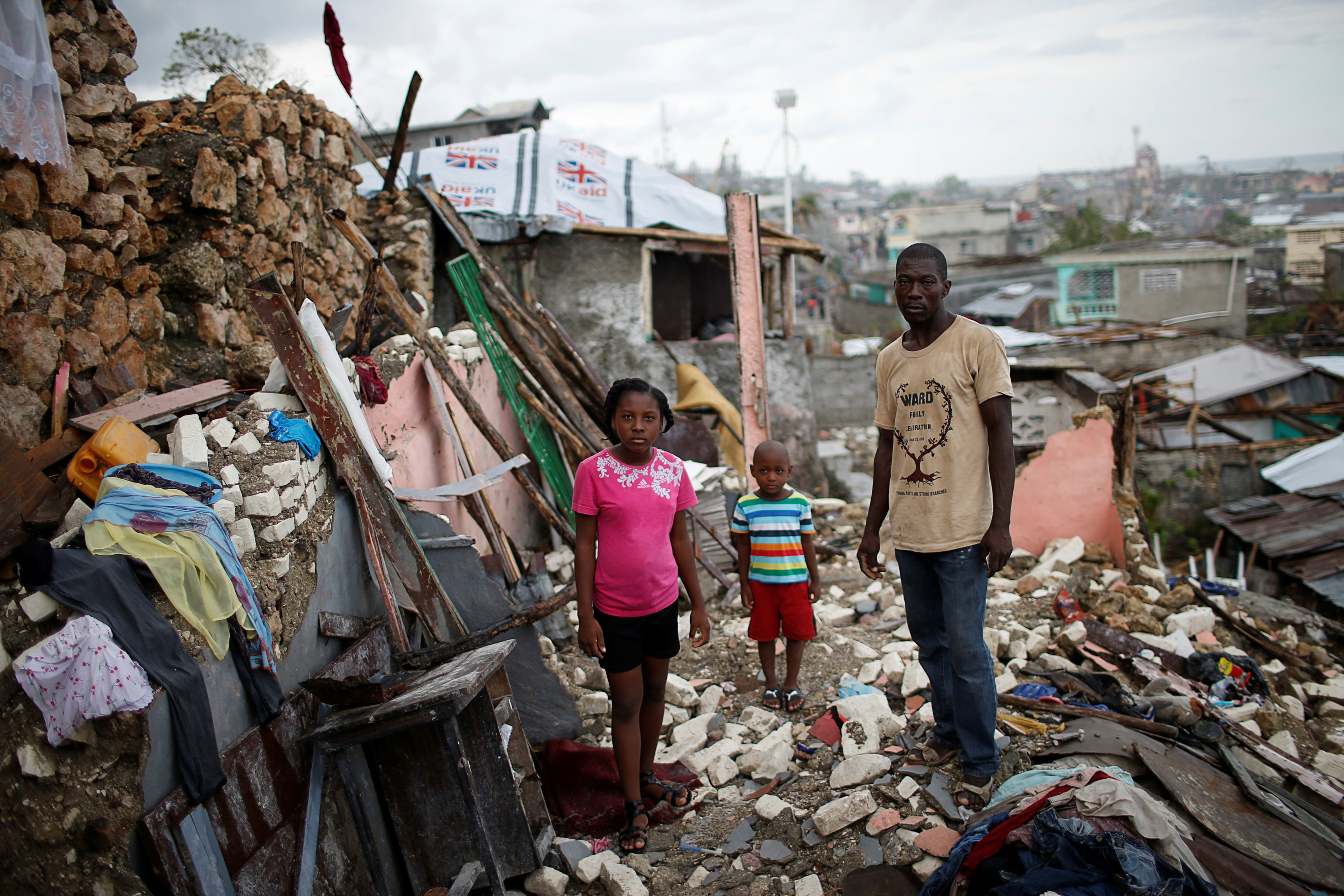 Prenille Nord, 42, poses for a photograph with his children Darline and Kervins among the debris of their destroyed house after Hurricane Matthew hit Jeremie, Haiti,