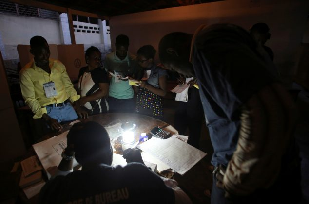 Electoral workers are seen during vote counting at a polling station as Haiti holds a long-delayed presidential election after a devastating hurricane and more than a year of political instability, in Port-au-Prince, Haiti,