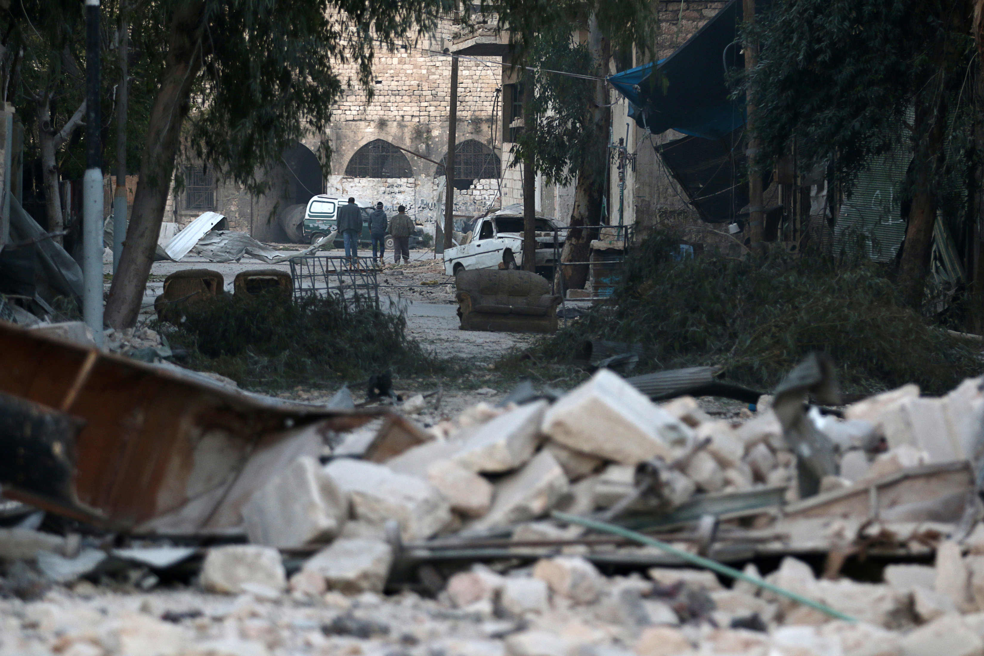 People walk near rubble of damaged buildings, in the rebel-held besieged area of Aleppo, Syria