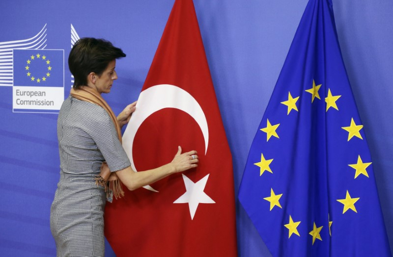 A woman adjusts the Turkish flag next to the European Union flag at the EU Commission headquarters in Brussels