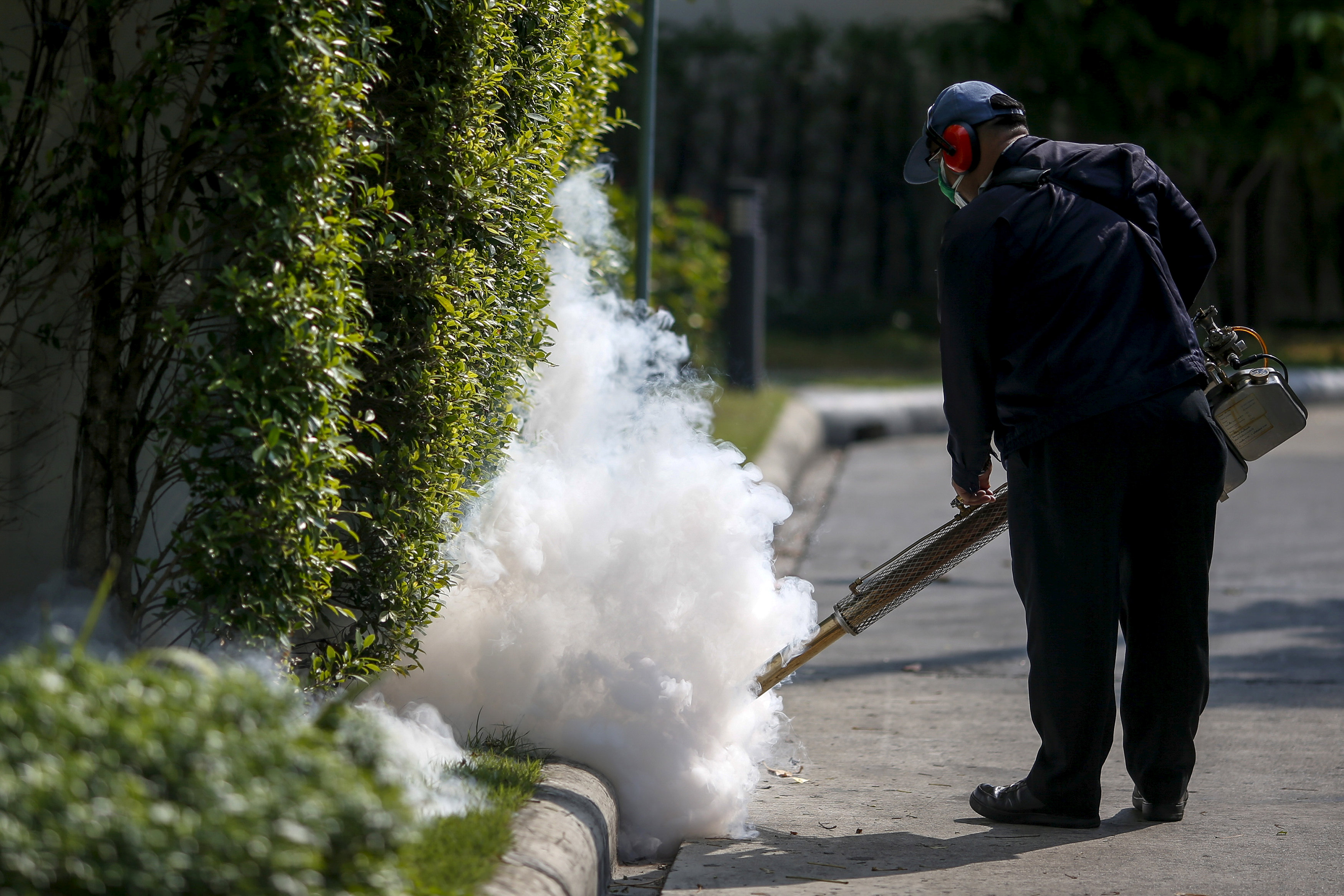 A worker sprays insecticide for mosquitos at a village in Bangkok, Thailand,