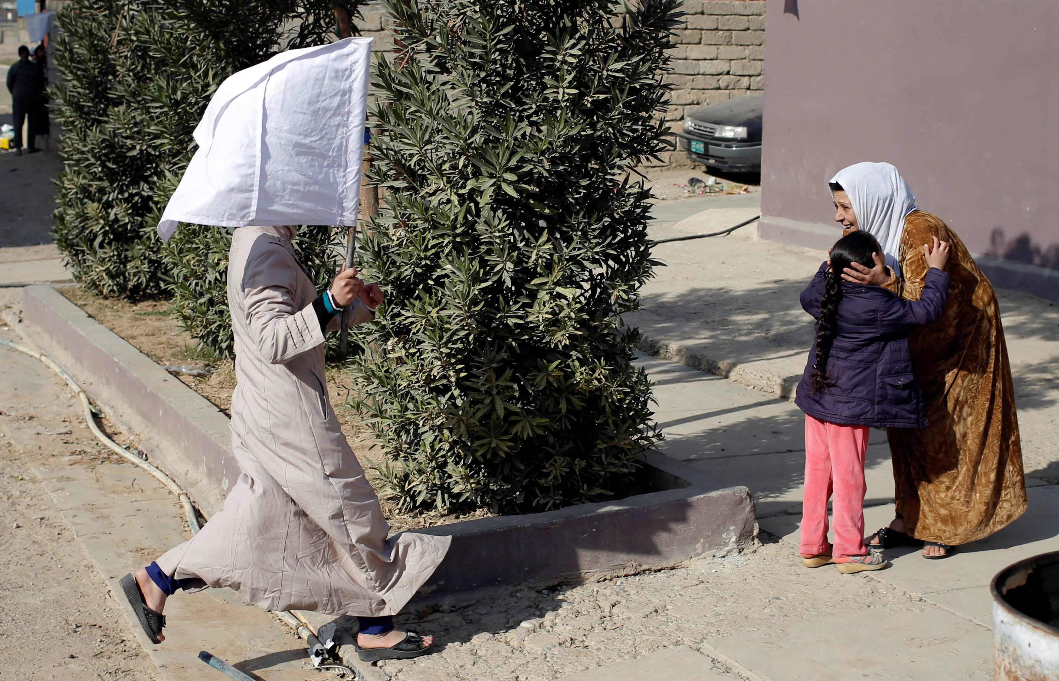 A woman holds up a white flag as she runs to greet her relative in Mosul, Iraq November