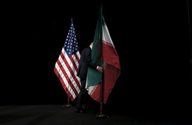 A staff member removes the Iranian flag from the stage after a group picture with foreign ministers and representatives of the U.S., Iran, China, Russia, Britain, Germany, France and the European Union during the Iran nuclear talks at the Vienna International Center in Vienna, Austria