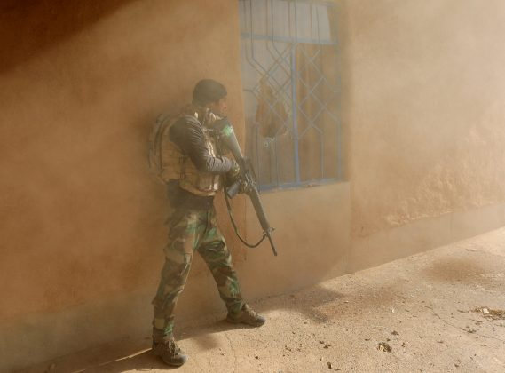 An Iraqi soldier searches a house during clashes with Islamic State fighters in Al-Qasar, southeast of Mosul.