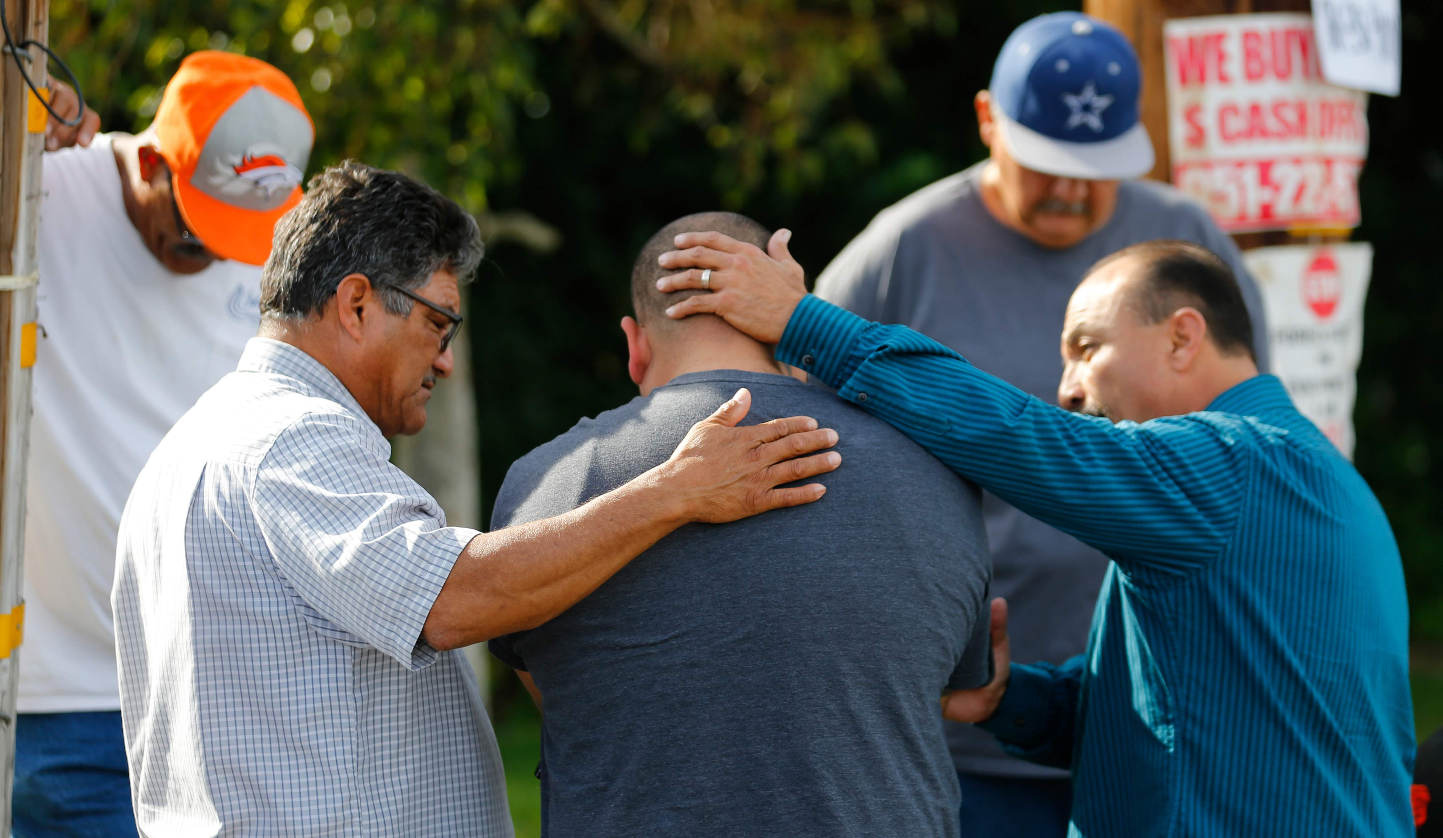Neighbours comfort Jose Gonzales (centre), who was prevented from returning to his wife and his home at the scene of the investigation around the area of the SUV vehicle where two suspects were shot by police following a mass shooting in San Bernardino, California December 3, 2015.