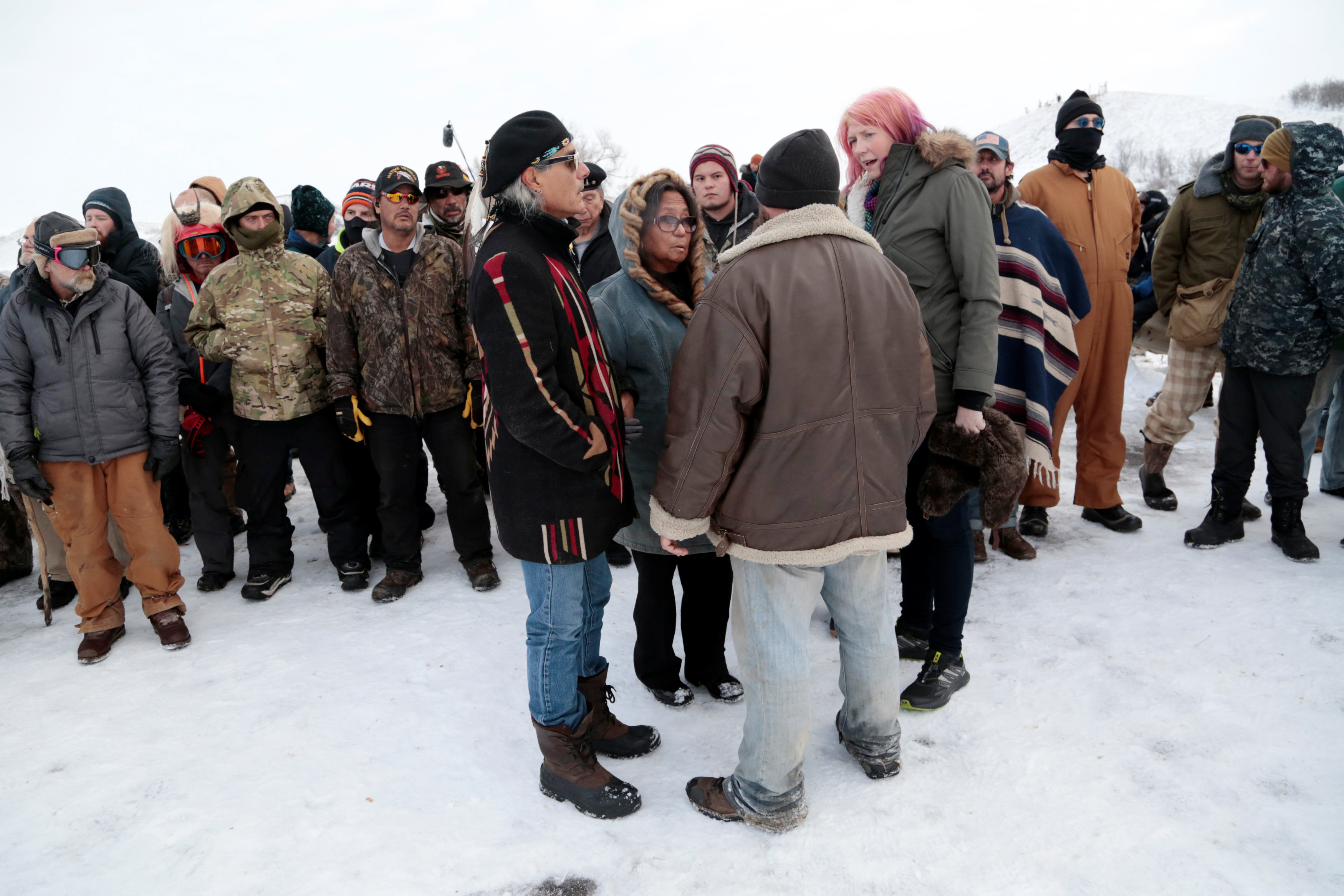 Phyllis Young (C) of the Standing Rock Sioux Tribe talks with veterans who oppose the Dakota Access oil pipeline and local law enforcement on Backwater Bridge near Cannon Ball, North Dakota,
