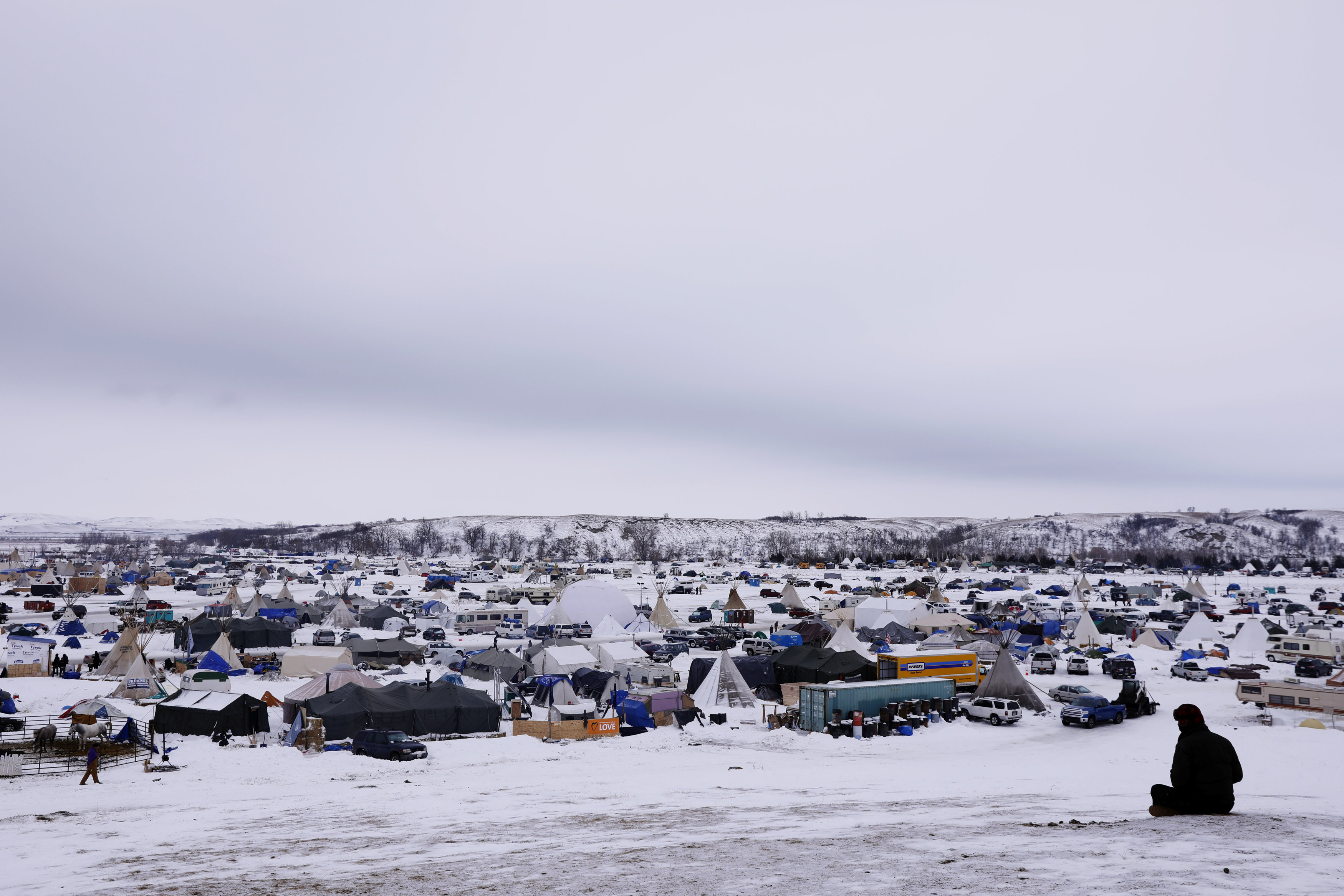 "A man rests on top of a hill inside of the Oceti Sakowin camp as ""water protectors"" continue to demonstrate against plans to pass the Dakota Access pipeline near the Standing Rock Indian Reservation, near Cannon Ball, North Dakota"