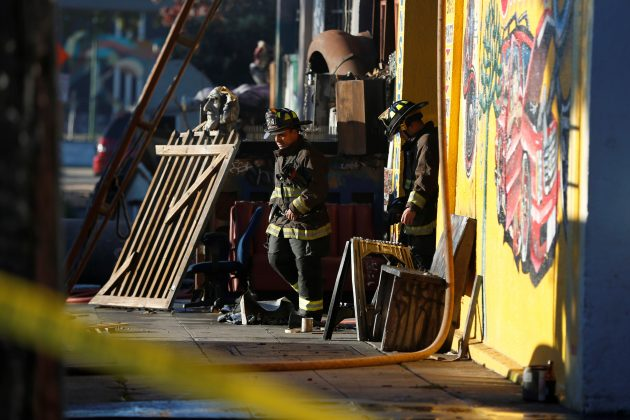 Firefighters exit a warehouse where a fire broke out during an electronic dance party late Friday evening, resulting in at least nine deaths and many unaccounted for in the Fruitvale district of Oakland, California, U.S