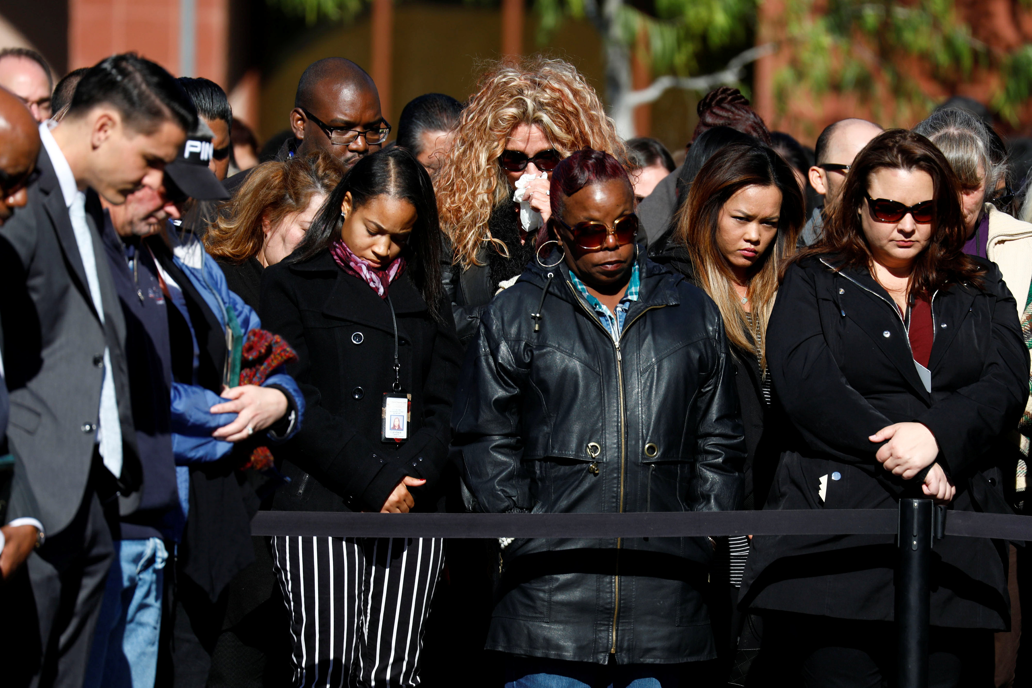 Attendees bow their heads during a memorial event at the Inland Regional Center on the one year anniversary of the San Bernardino attack in San Bernardino, California, U.S.