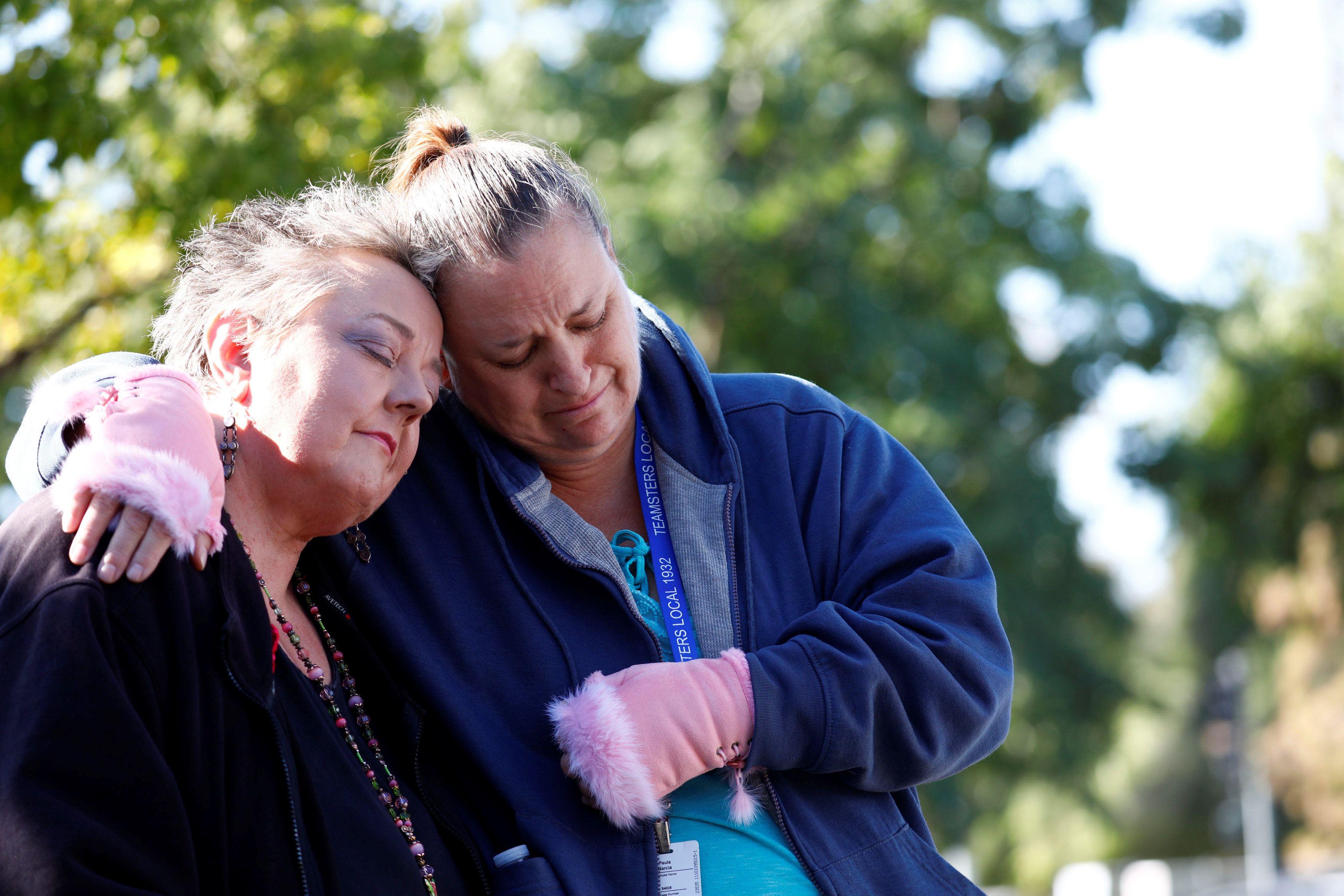 San Bernardino County employees Zen Martinsen (L) and Paula Garcia (R), hug during a memorial event at the Inland Regional Center on the one year anniversary of the San Bernardino attack in San Bernardino,