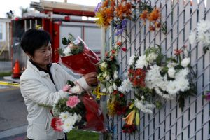 woman placing flowers at memorial