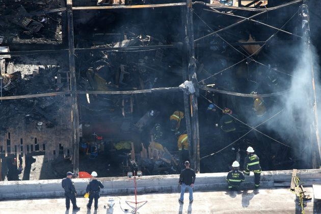 Firefighters work inside the burned warehouse following the fatal fire in the Fruitvale district of Oakland, California.