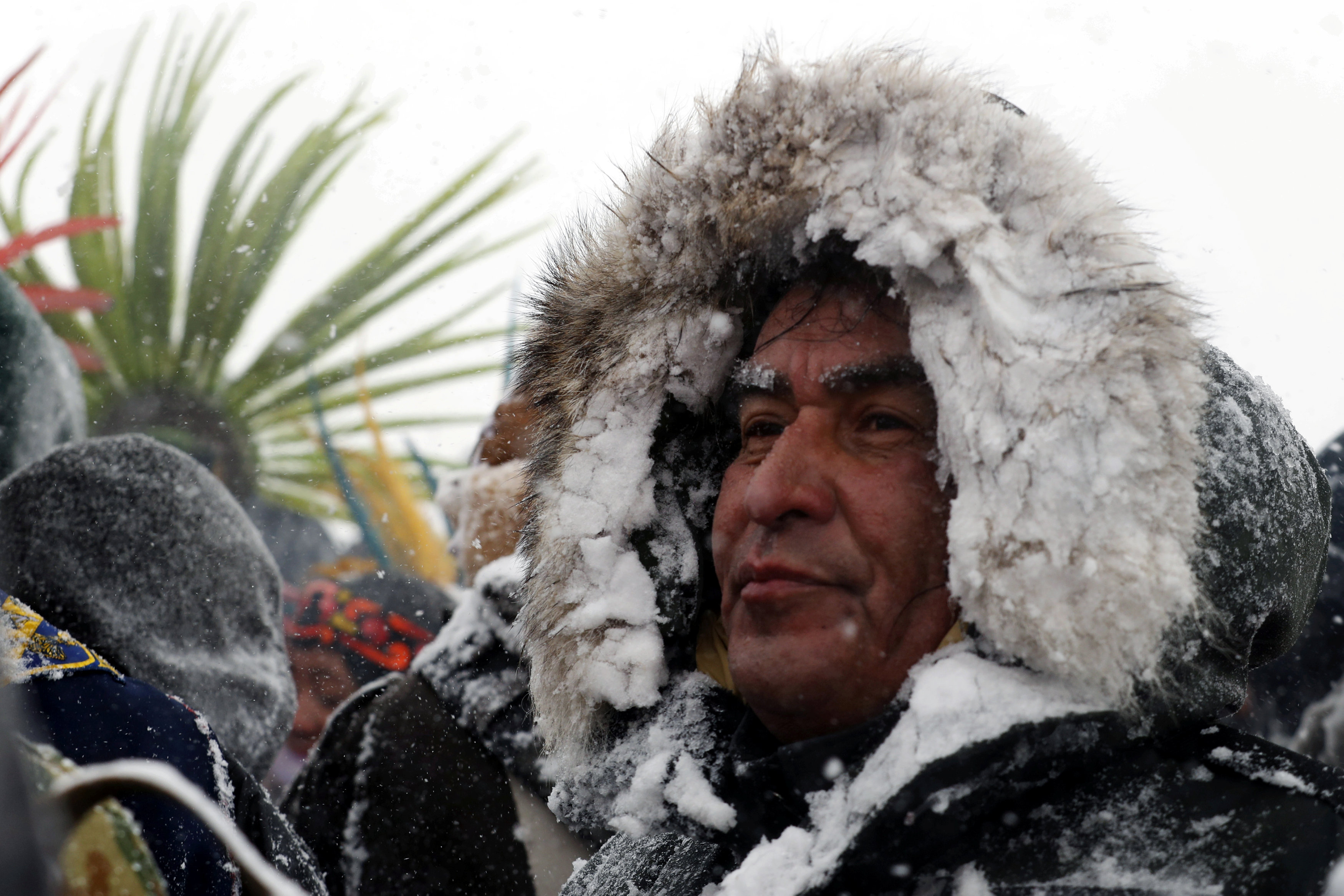 "A Native American man stands in the snow during a march with veterans near Backwater Bridge just outside of the Oceti Sakowin camp during a snow fall as ""water protectors"" continue to demonstrate against plans to pass the Dakota Access pipeline adjacent to the Standing Rock Indian Reservation, near Cannon Ball, North Dakota,"
