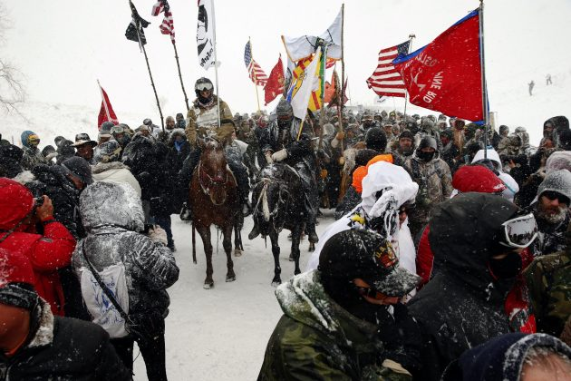 "Veterans march with activists near Backwater Bridge just outside the Oceti Sakowin camp during a snow fall as ""water protectors"" continue to demonstrate against plans to pass the Dakota Access pipeline"