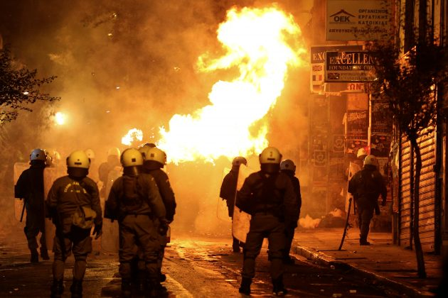 A petrol bomb explodes next to riot police during clashes following an anniversary rally marking the 2008 police shooting of 15-year-old student, Alexandros Grigoropoulos, in Athens, Greece,