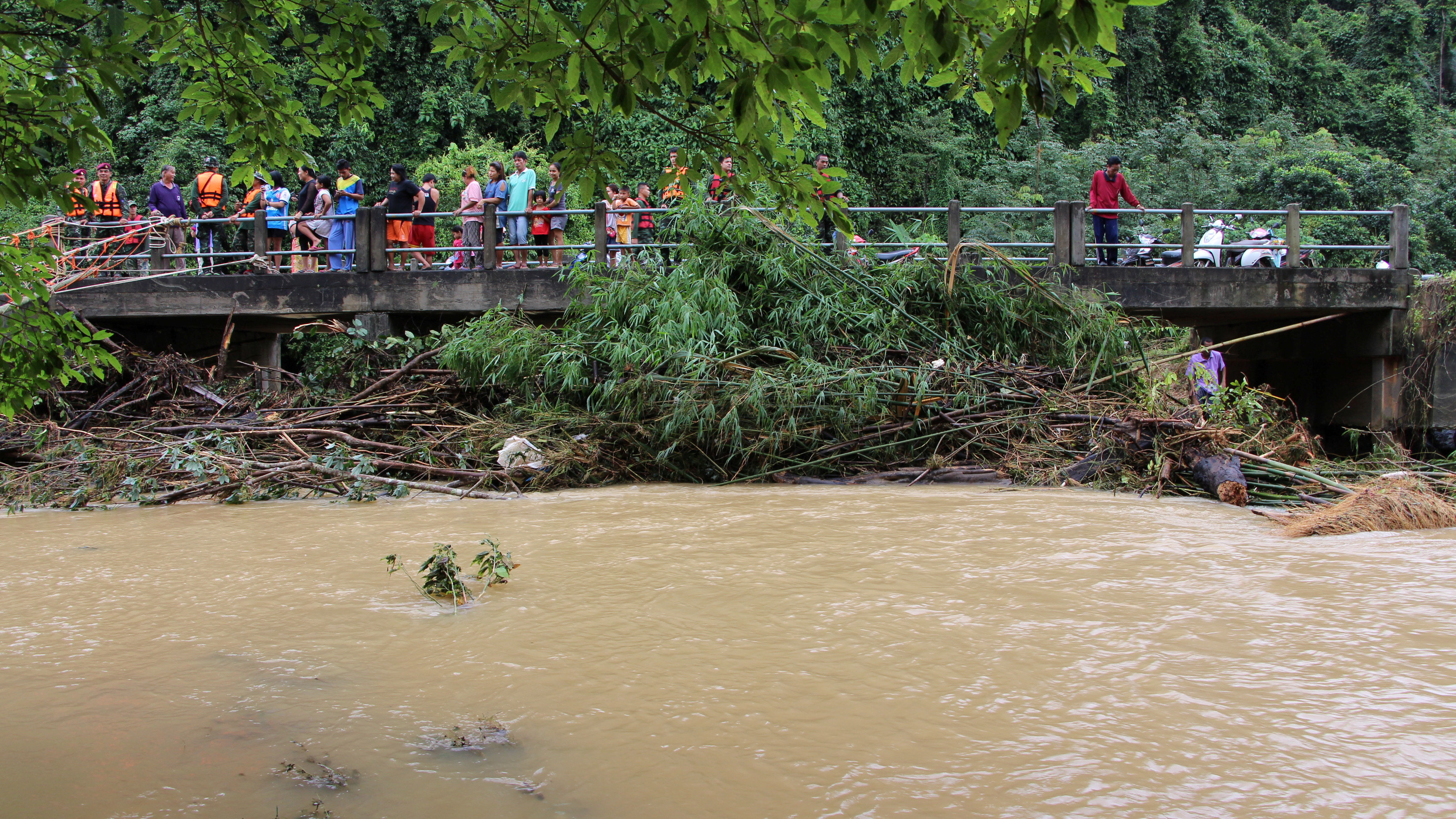 Onlookers and rescue workers stand on a bridge in a flooded area in Sichon District, Nakhon Si Thammarat province, Thailand December