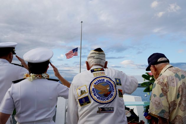 Pearl Harbor survivors Delton Walling (C), Gilbert Meyer (R) and U.S. Navy Admiral Margaret Kibben salute during a ceremony honoring the sailors of the USS Utah at the memorial on Ford Island at Pearl Harbor in Honolulu, Hawaii