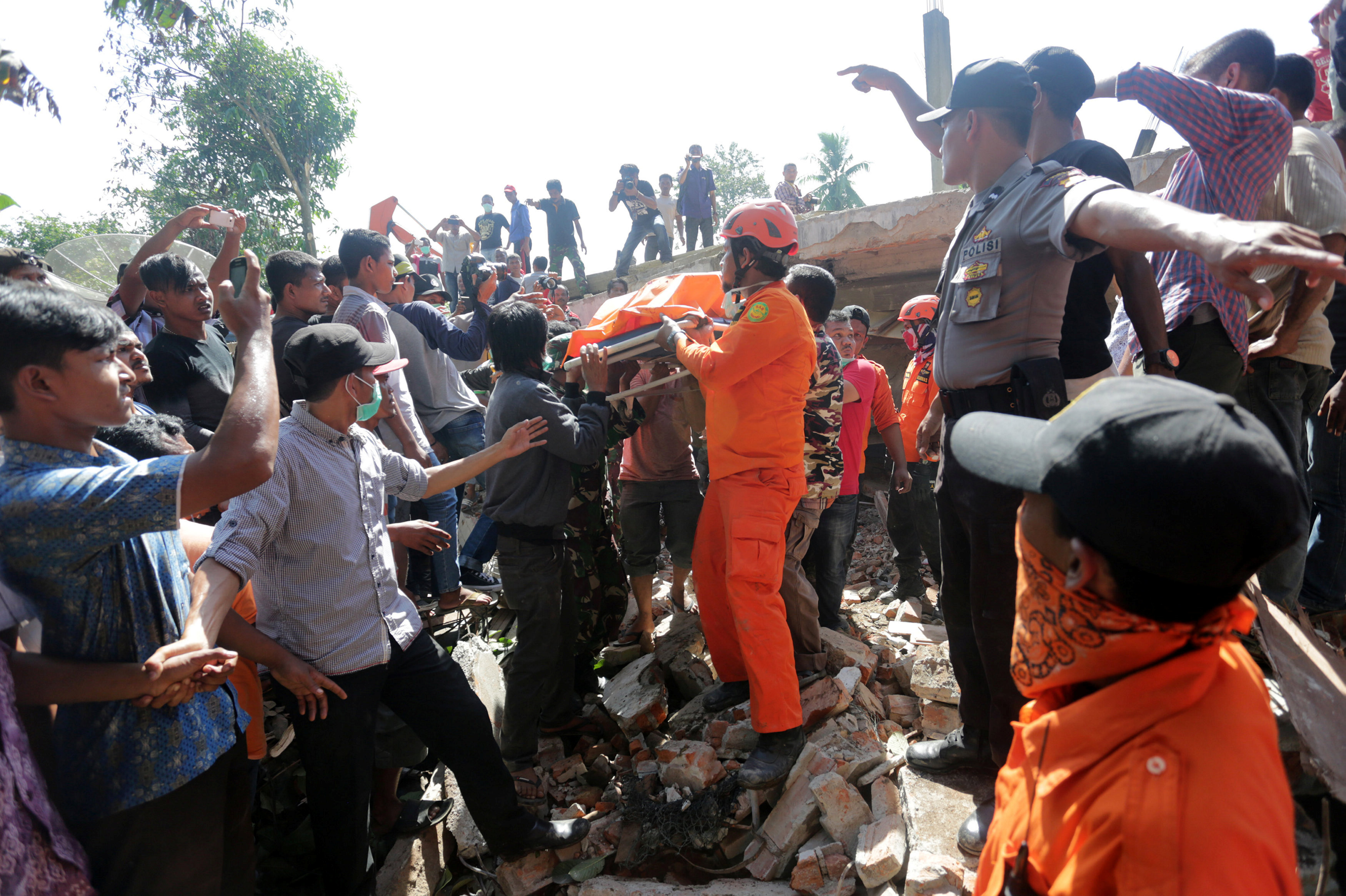 Rescue workers and police remove a victim from a collapsed building following an earthquake in Lueng Putu, Pidie Jaya in the northern province of Aceh, Indonesia